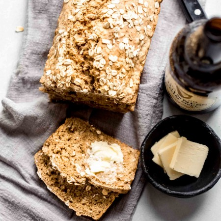 Overhead shot of guinness bread next to bottle of beer and pats of butter.