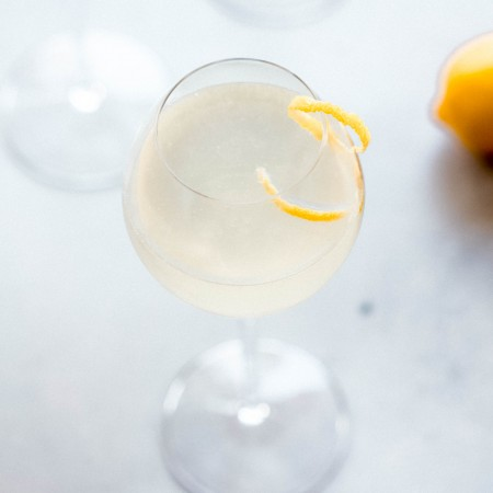 Side view of French 75 cocktail garnished with lemon twist.