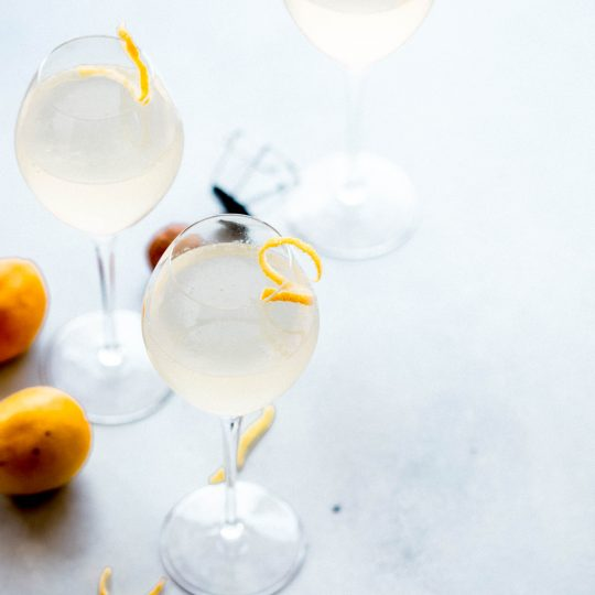 Three French 75 cocktails garnished with lemon twists.