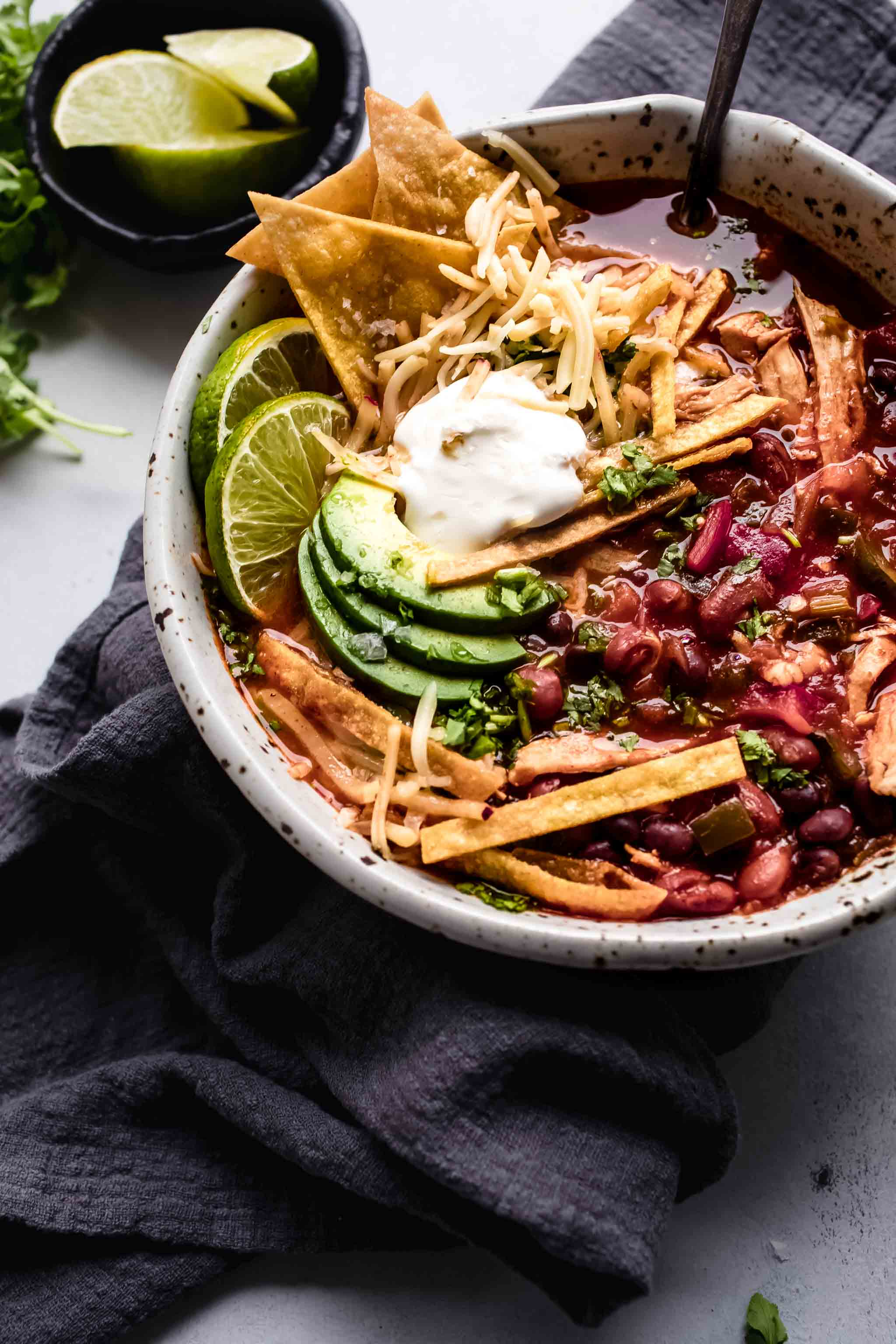 Overhead close up of bowl of Instant Pot Chicken Tortilla Soup topped with avocado, tortilla chips and sour cream.