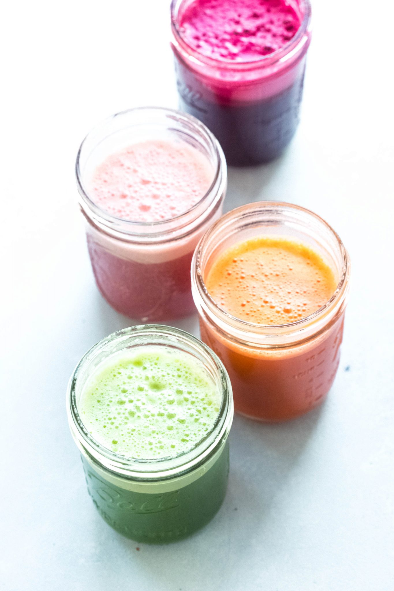 Four different colorful juices in a row in mason jars.