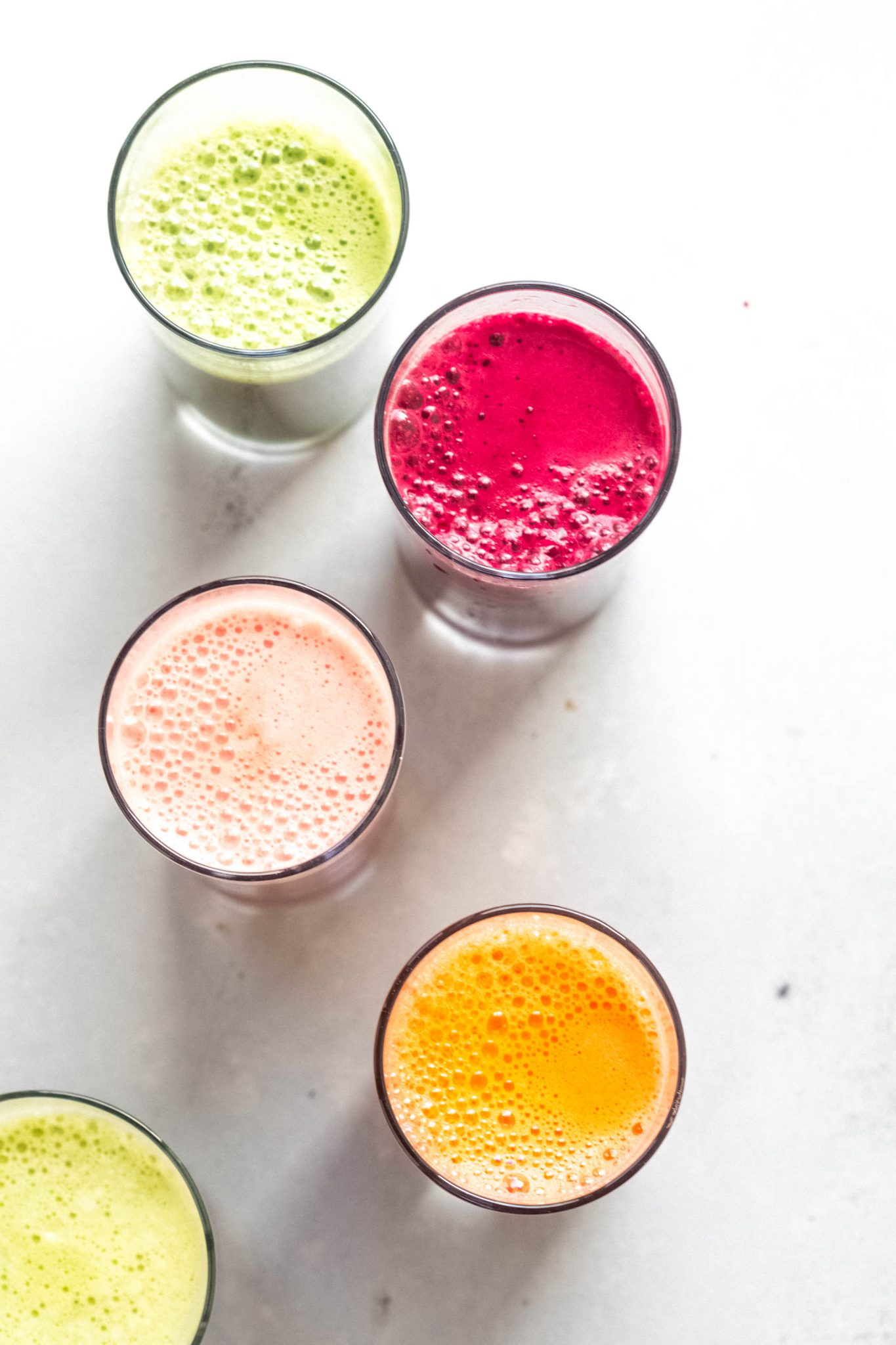 Five different colorful juices in a row shot from overhead.