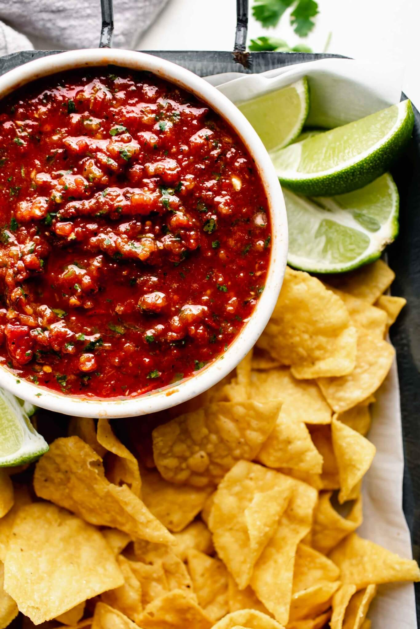 Bowl of chipotle salsa in serving tray with chips and limes.