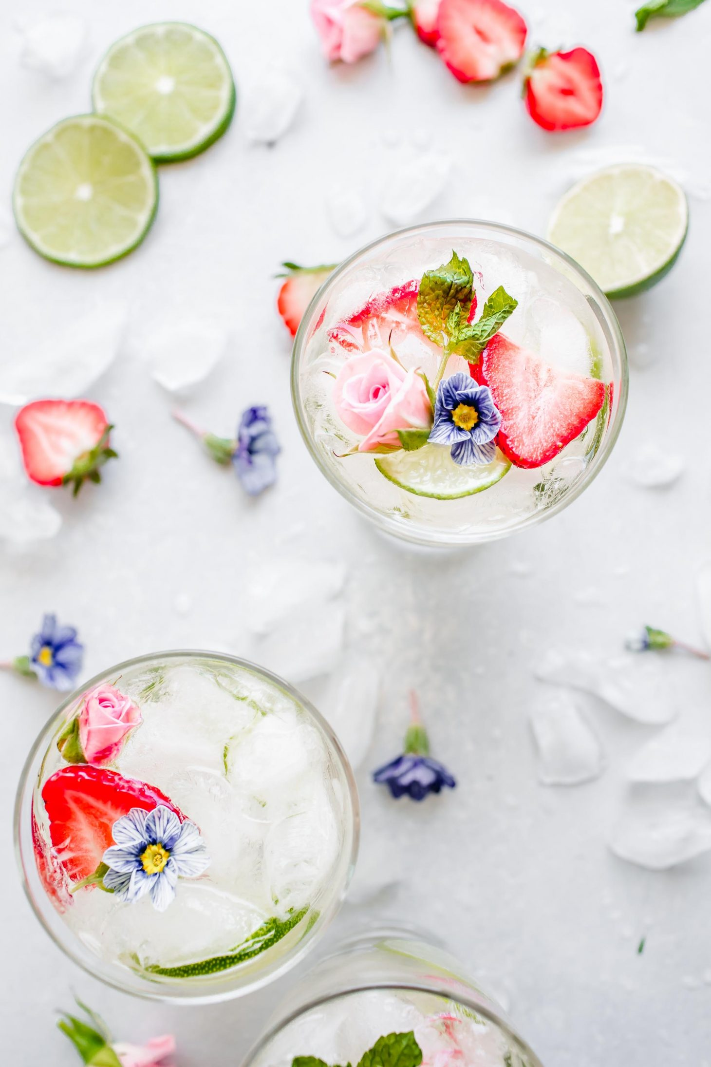 Overhead shot of three glasses of white wine sangria topped with edible flowers.