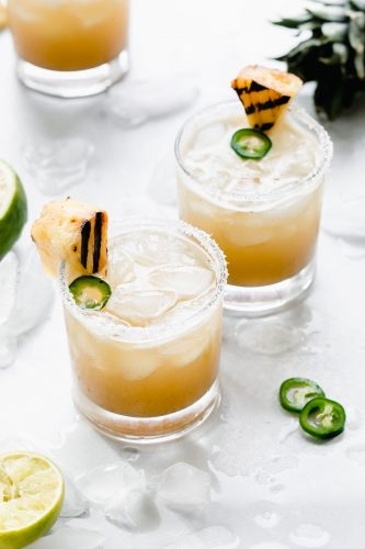 Side view of grilled pineapple margarita garnished with grilled pineapple and jalapeno.