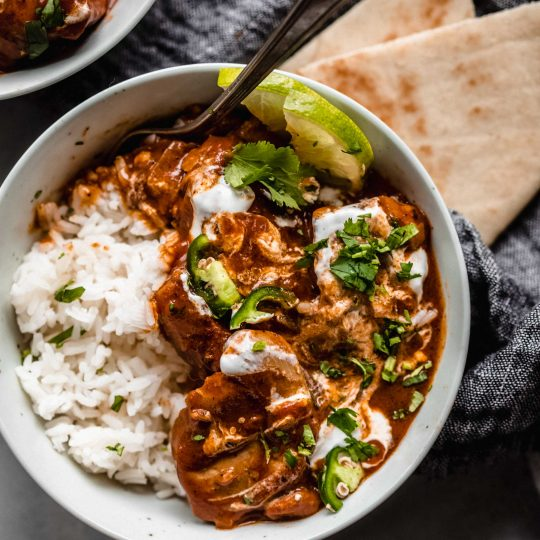 Instant Pot Butter Chicken in bowl served with lime wedges and naan.