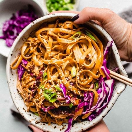 Two hands holding bowl of sesame noodles.