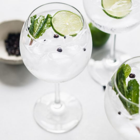 Three glasses of gin tonic cocktail garnished with limes and mint.