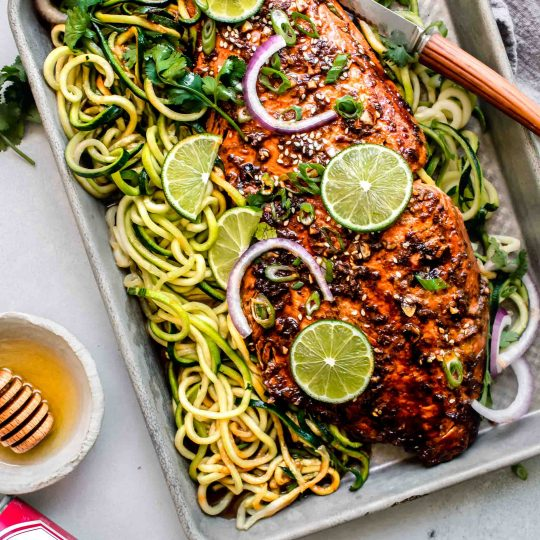 Overhead shot of salmon on baking sheet with zoodles.