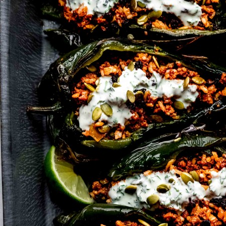 Overhead shot of stuffed poblanos arranged in baking dish drizzled with lime crema.