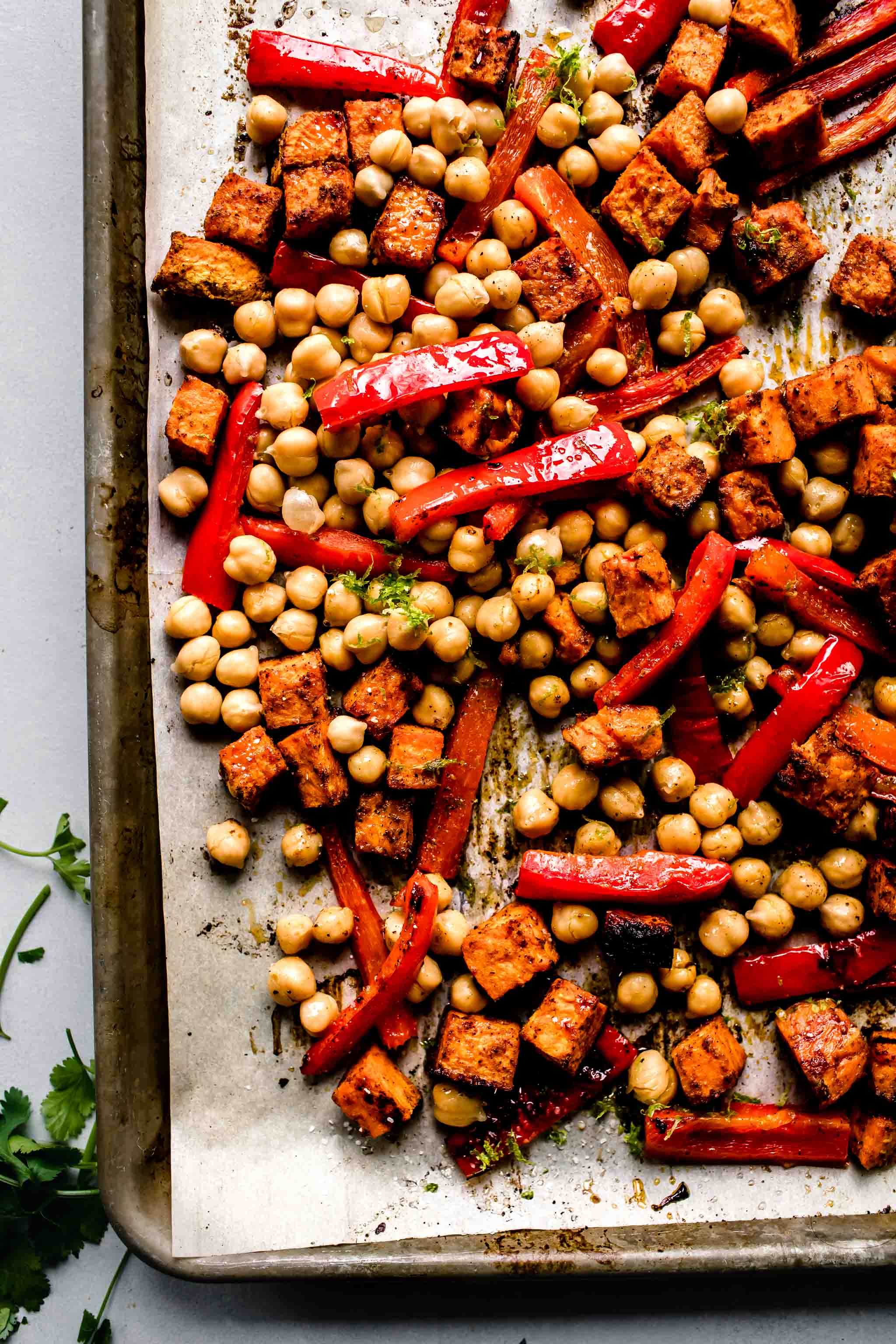 Peppers, sweet potatoes and chickpeas on baking sheet after roasting.