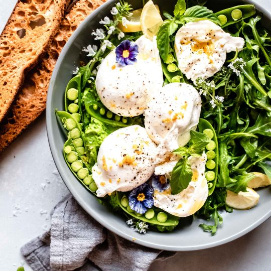 Burrata and sweet peas arranged on grey plate with arugula salad and crostini.