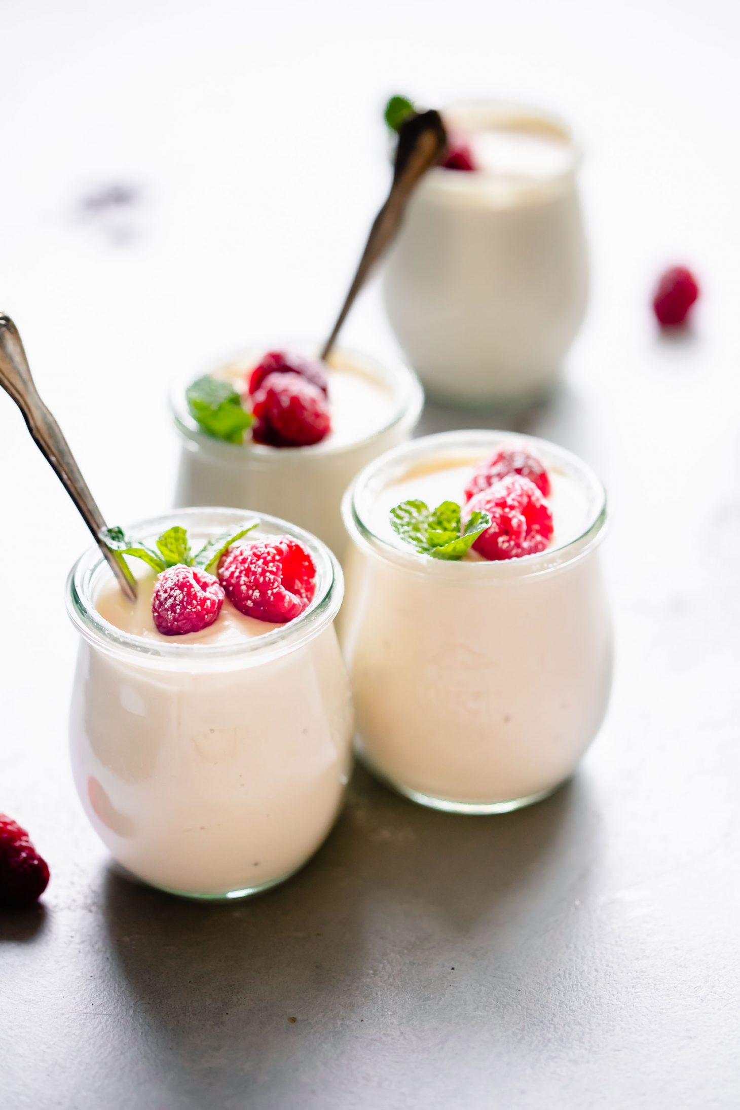 Four jars of ricotta mousse topped with raspberries.