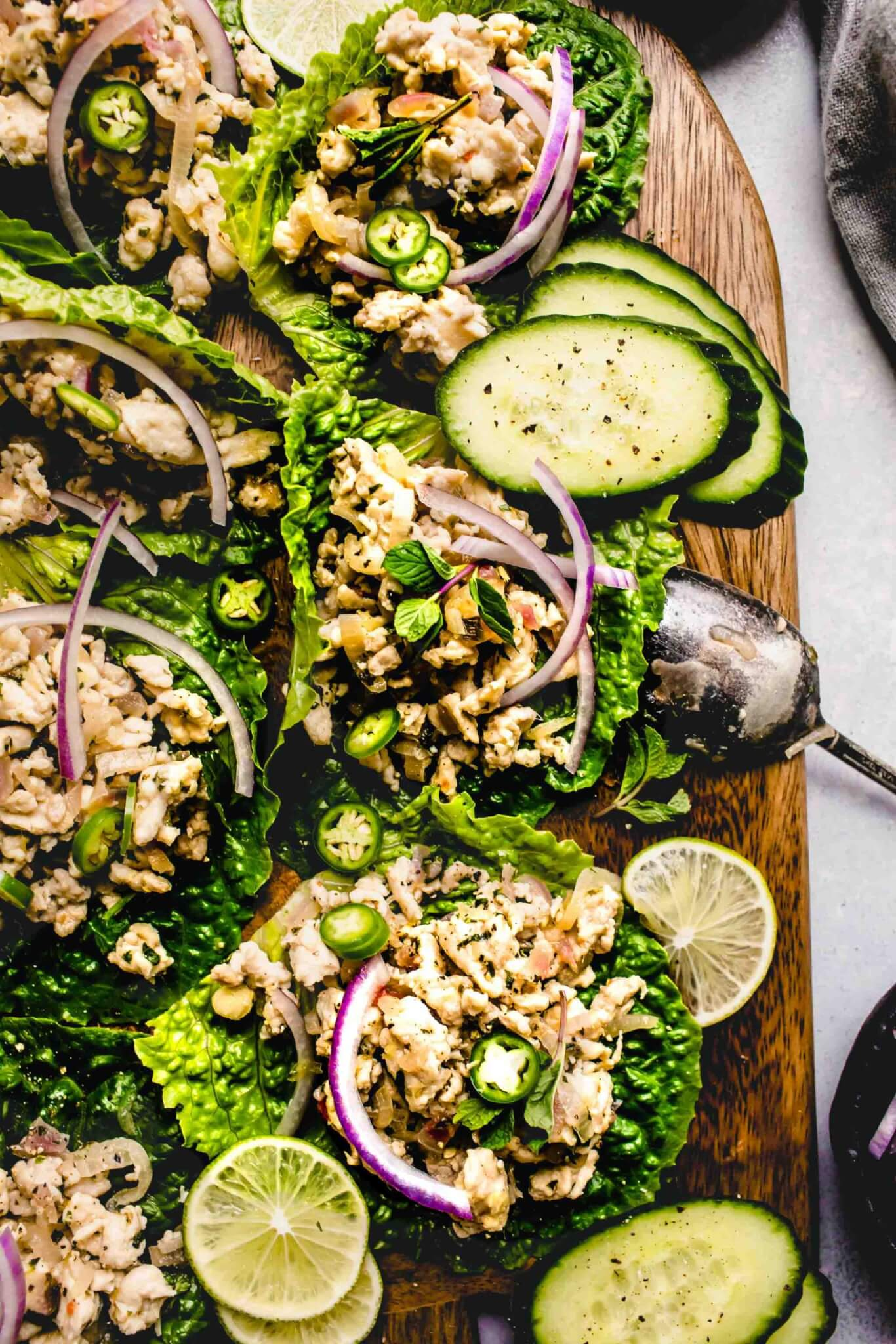 Larb gai lettuce wraps arranged on wood serving tray garnished with red onions and cucumber slices.