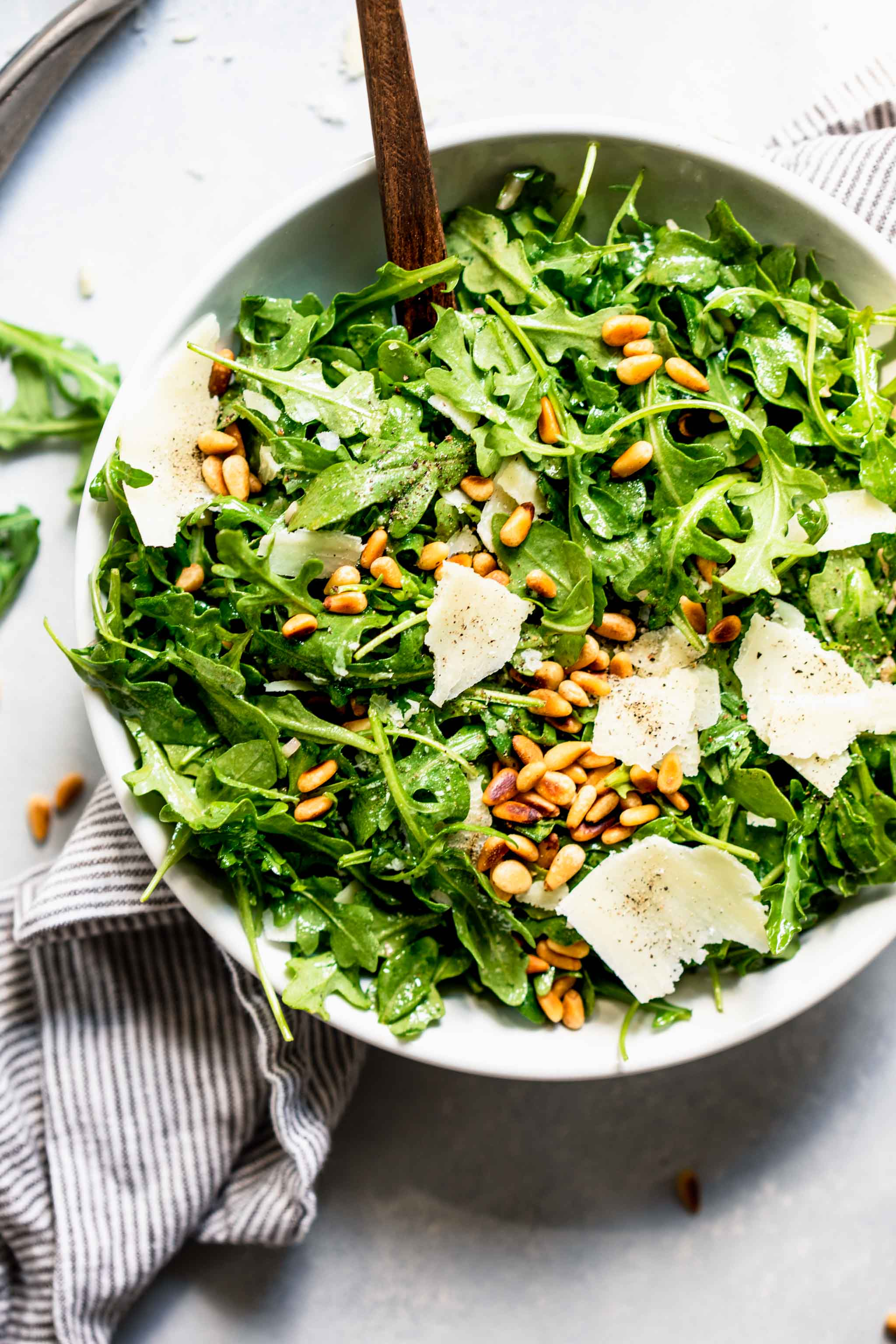 Overhead shot of arugula salad next to bowl of pine nuts and shaved parmesan.
