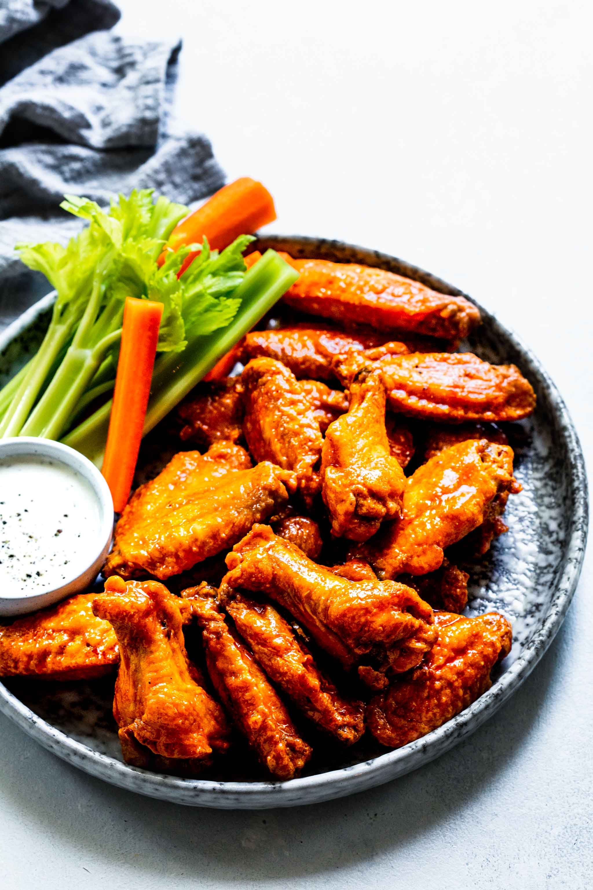 Baked buffalo wings coated in buffalo sauce on grey speckled plate next to blue cheese and celery sticks.