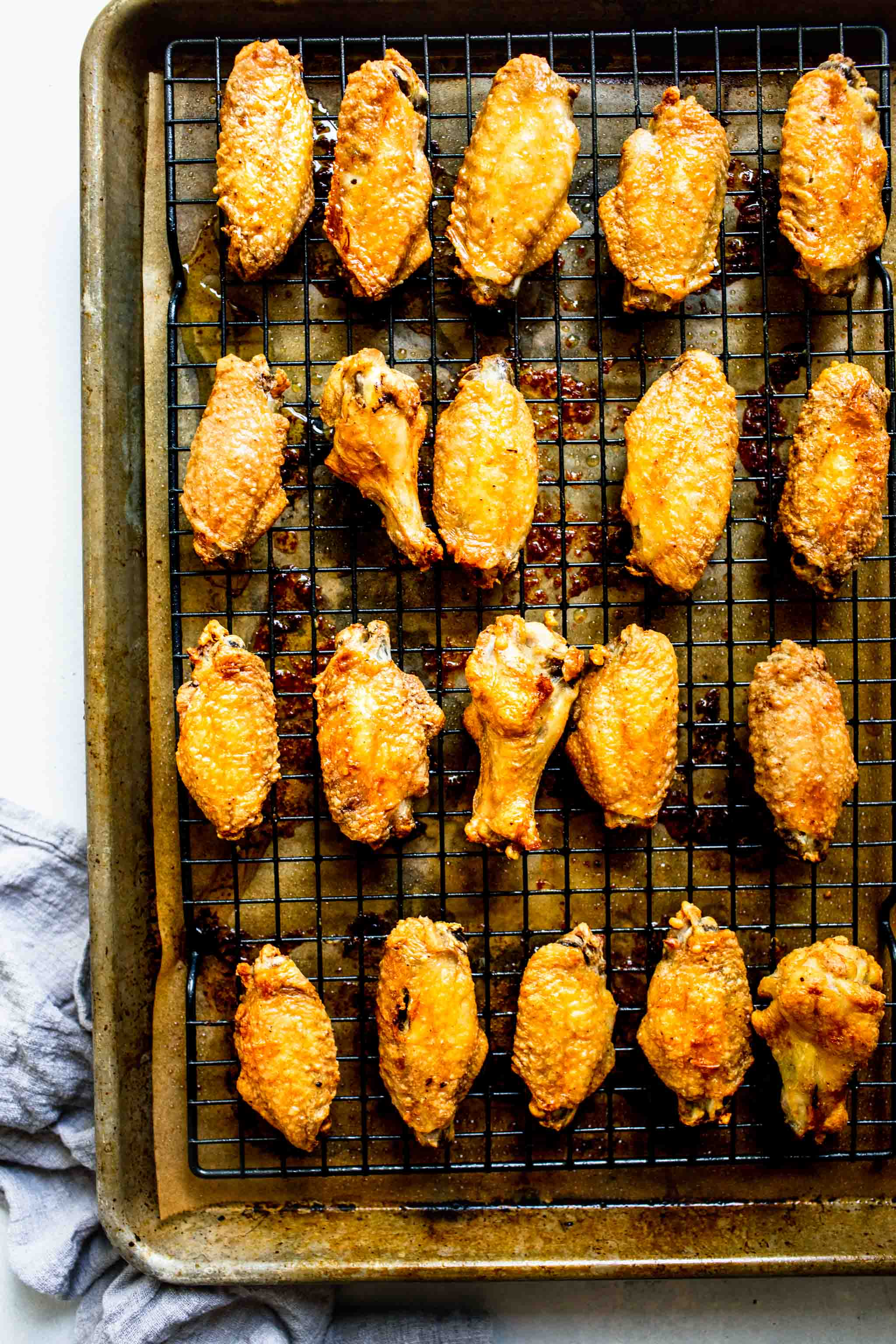 Baked buffalo wings on baking sheet.