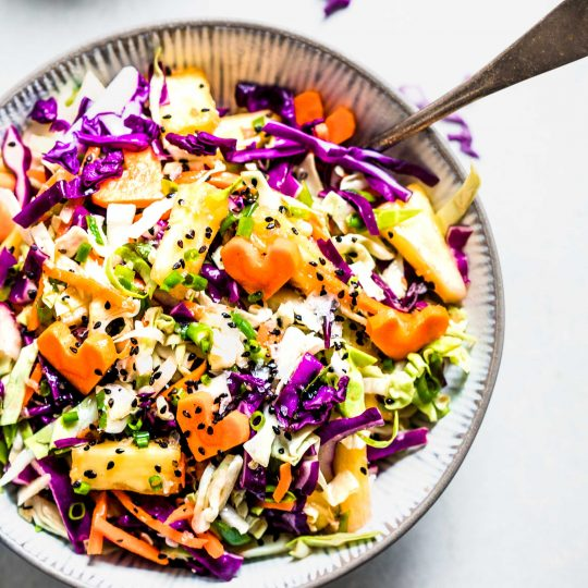 Overhead shot of bowl of Hawaiian Coleslaw topped with black sesame seeds and heart shaped carrots.