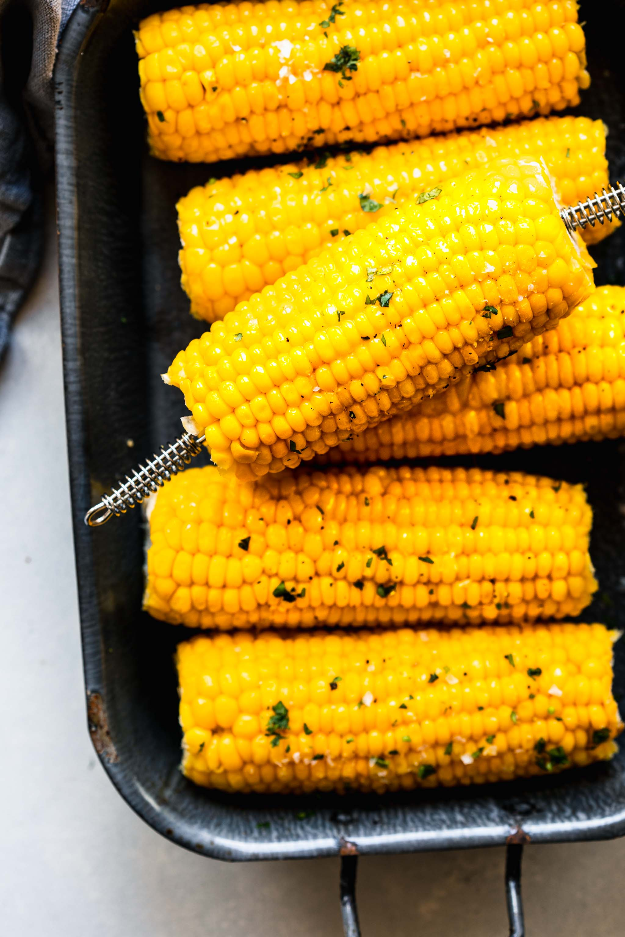 Cooked ears of corn on the cob in grey serving dish.