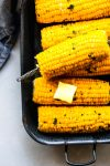 Ears of corn on the cob in a grey serving dish with a pat of butter and sprinkling of parsley.
