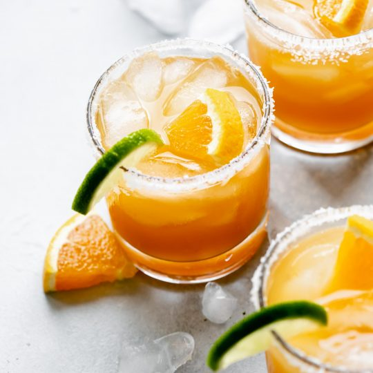 Three glasses of Italian Margarita rimmed with salt and garnished with orange and lime slices.