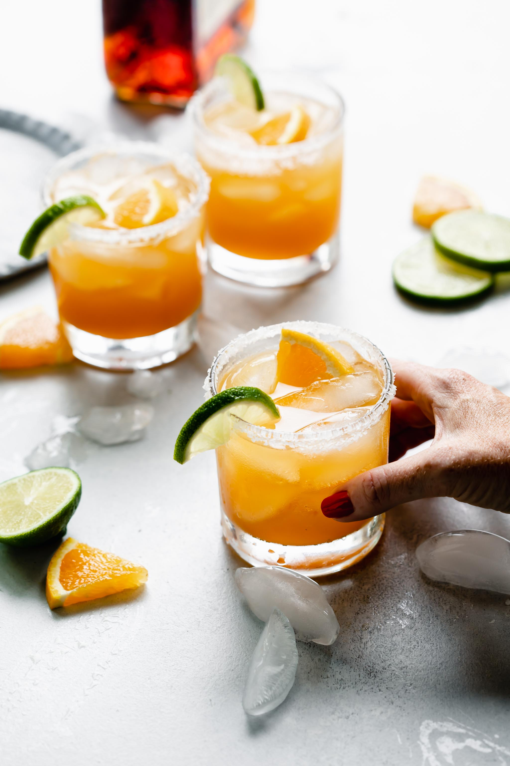 Hand holding glass of Italian Margarita rimmed with salt and garnished with orange and lime slices.