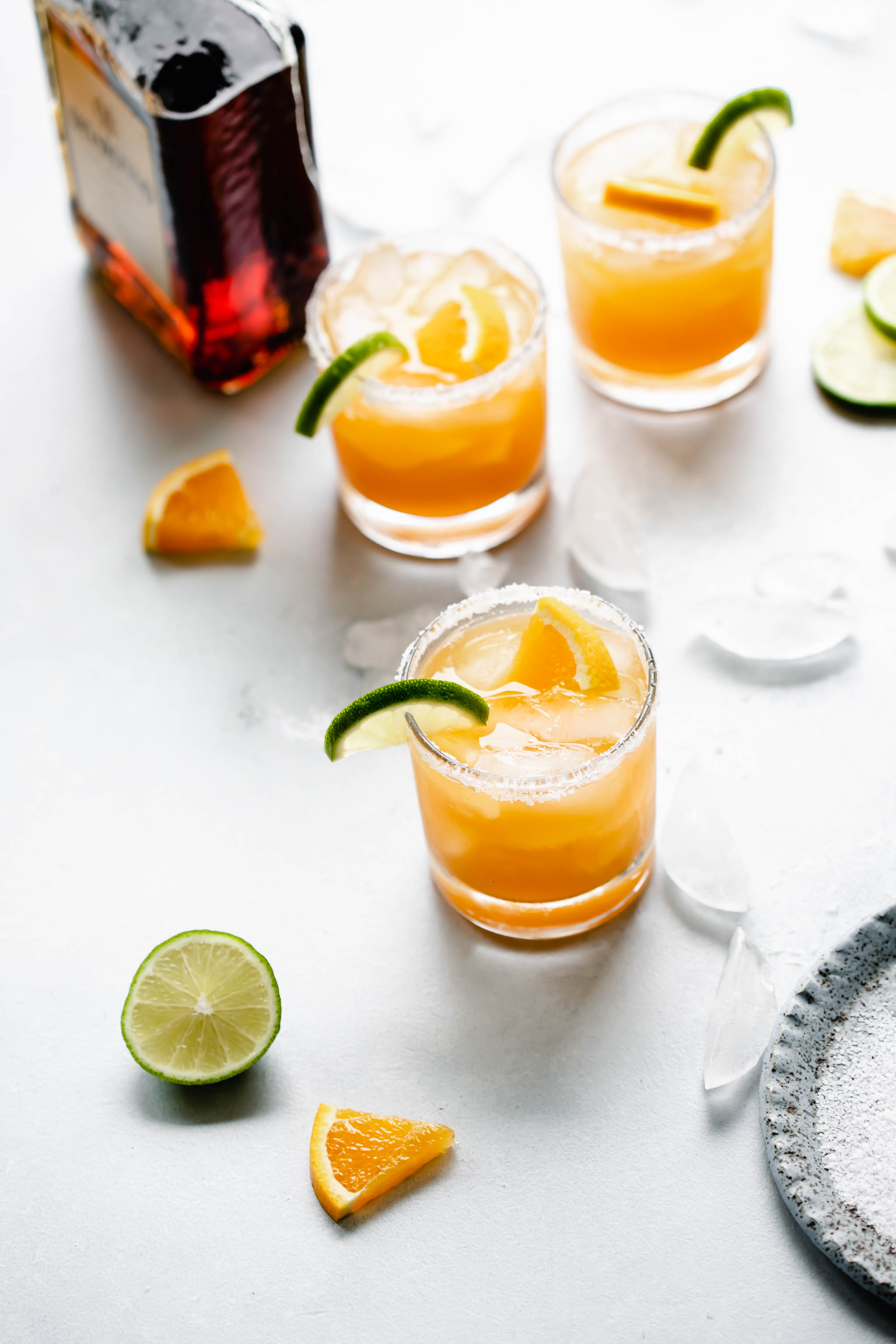 Three glasses of Italian Margarita rimmed with salt and garnished with orange and lime slices next to bottle of amaretto liqueur.