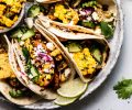 Mexican Street Corn Tacos arranged on grey plate next to bowl of corn.