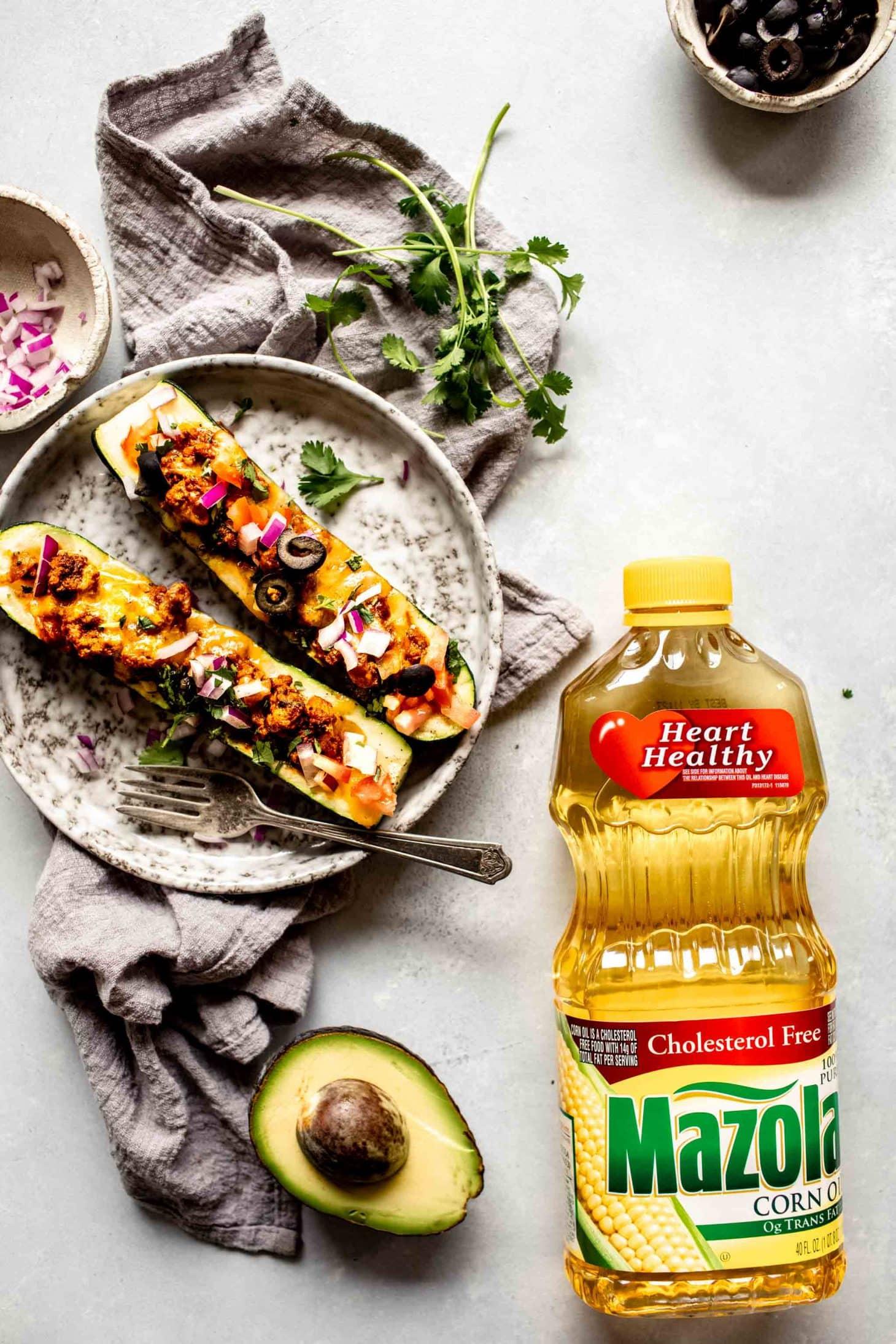 Two zucchini taco boats on grey plate next to cilantro, avocado and corn oil.
