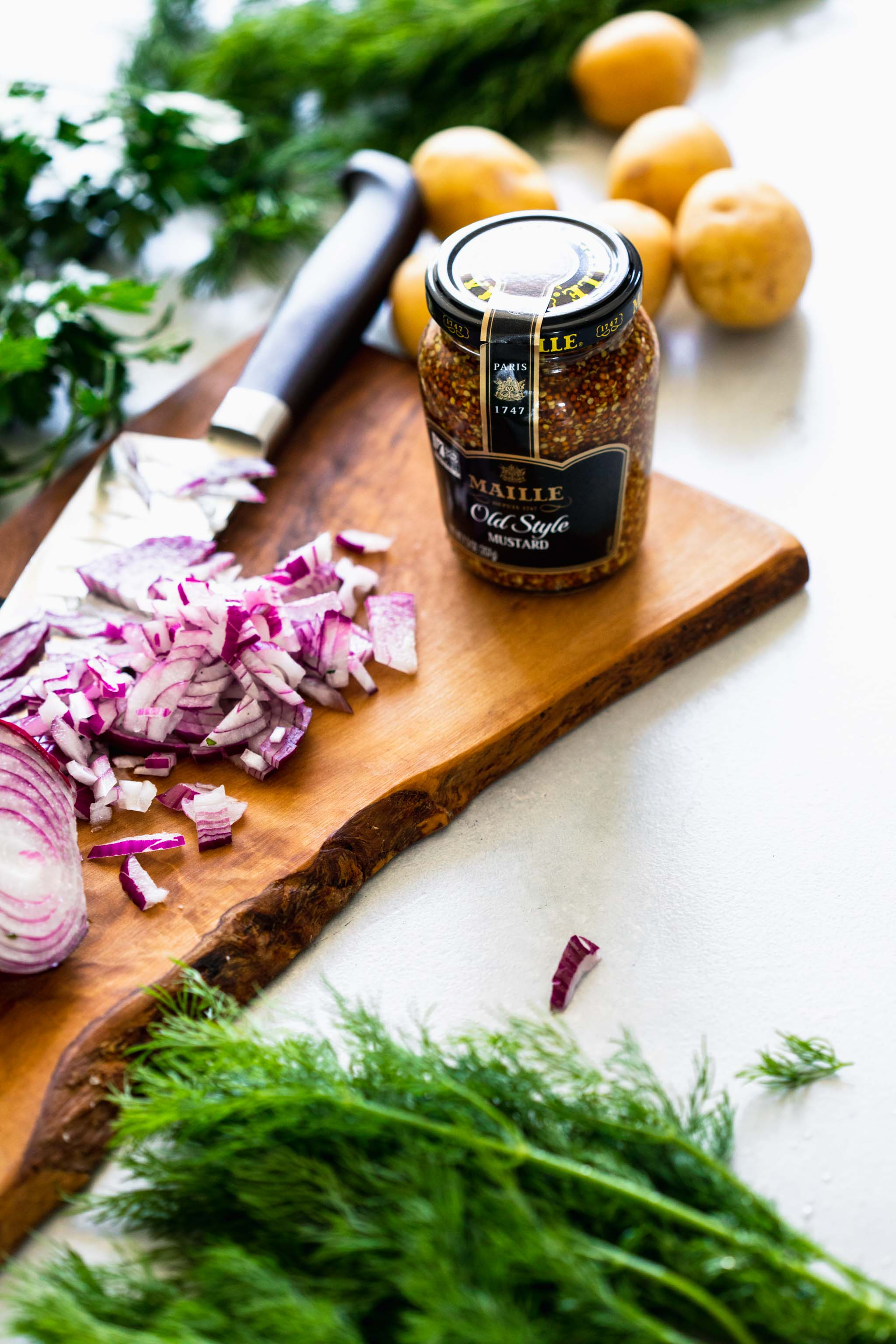 Jar of mustard next to chopped red onions on cutting board.