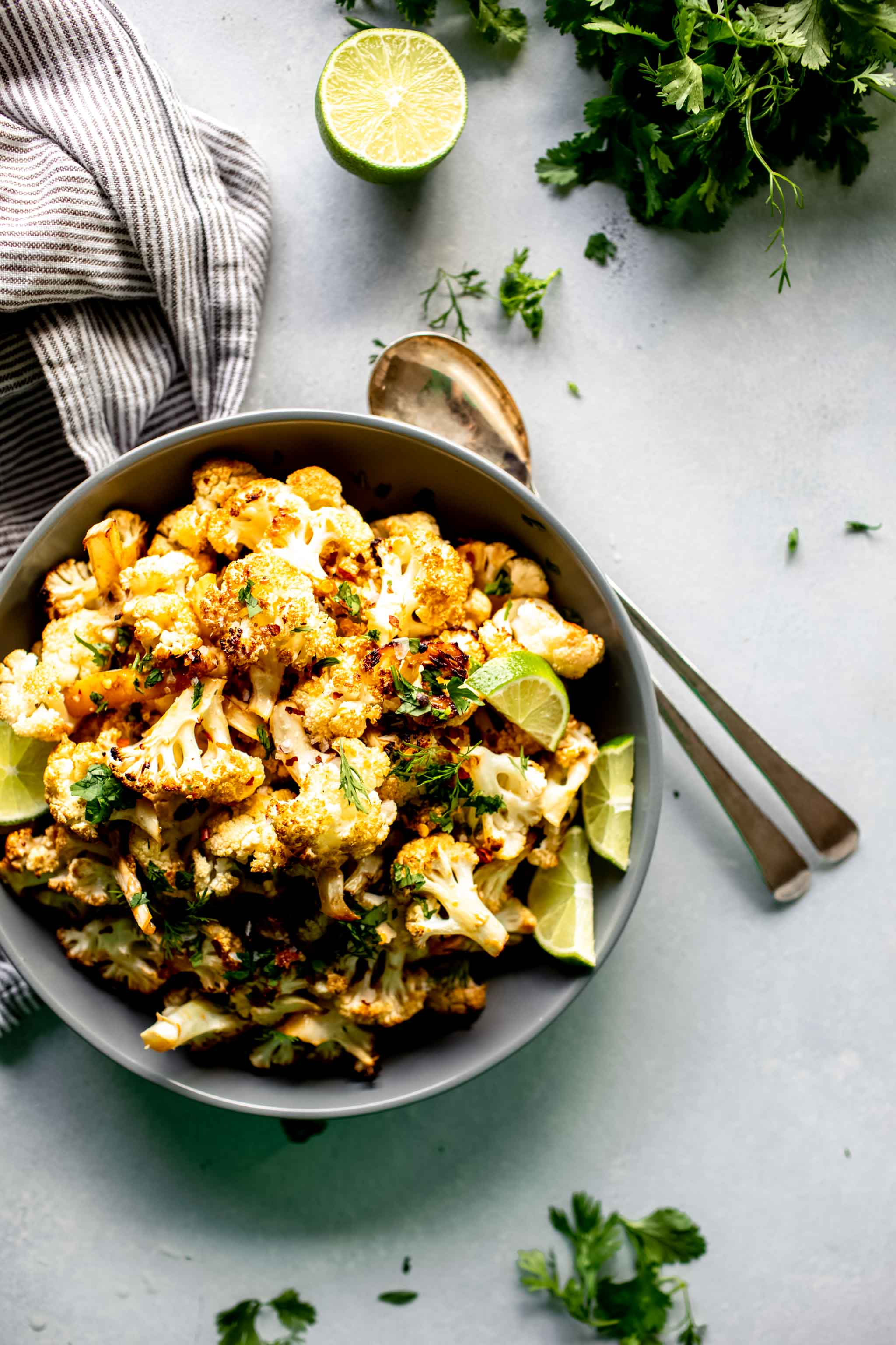 Overhead shot of bowl of roasted cauliflower on grey table next to bunch of cilantro, lime and serving spoons.
