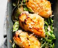 Overhead shot of three chicken breasts glazed with miso in grey pan served over pea pods.