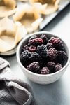 Bowl of frozen blackberries next to muffin tin.