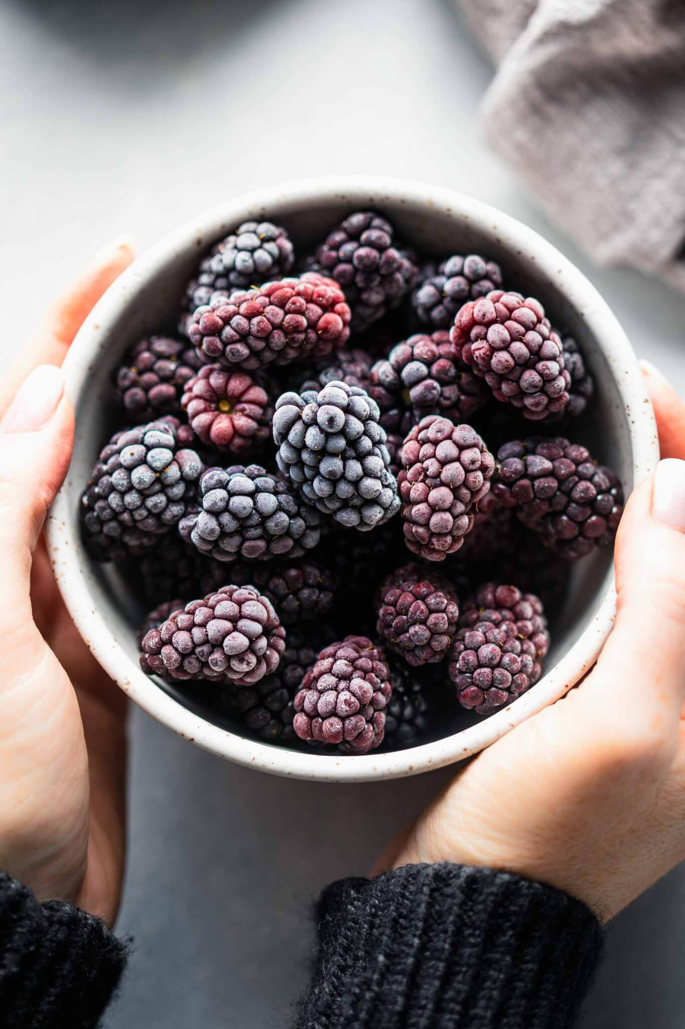 Hands holding bowl of frozen blackberries.