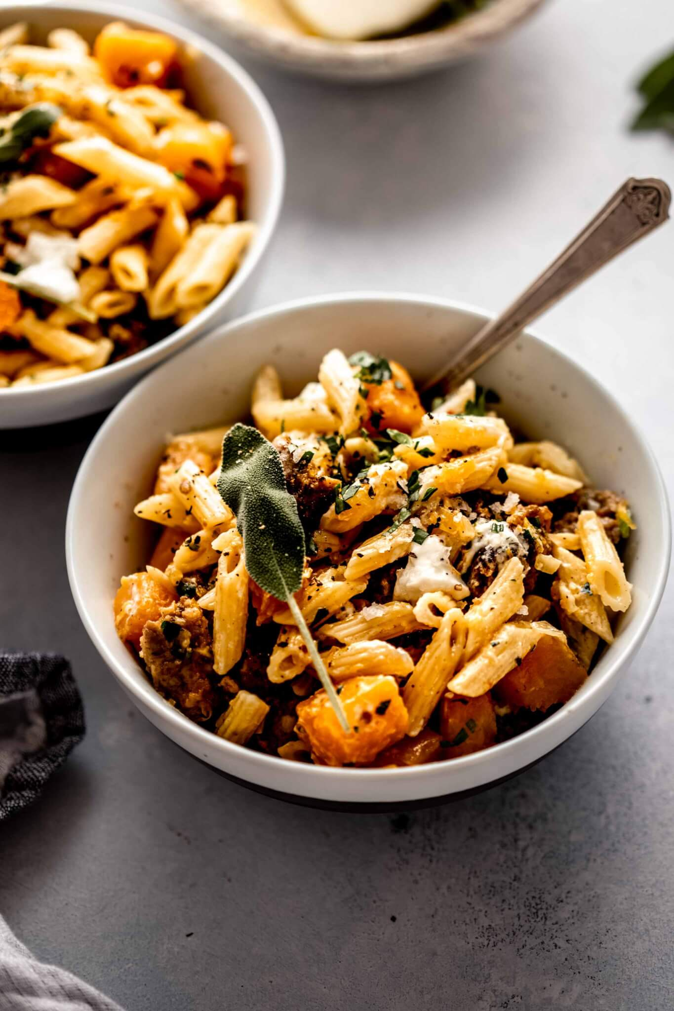 Two bowls of butternut squash pasta topped with sage leaves and goat cheese.