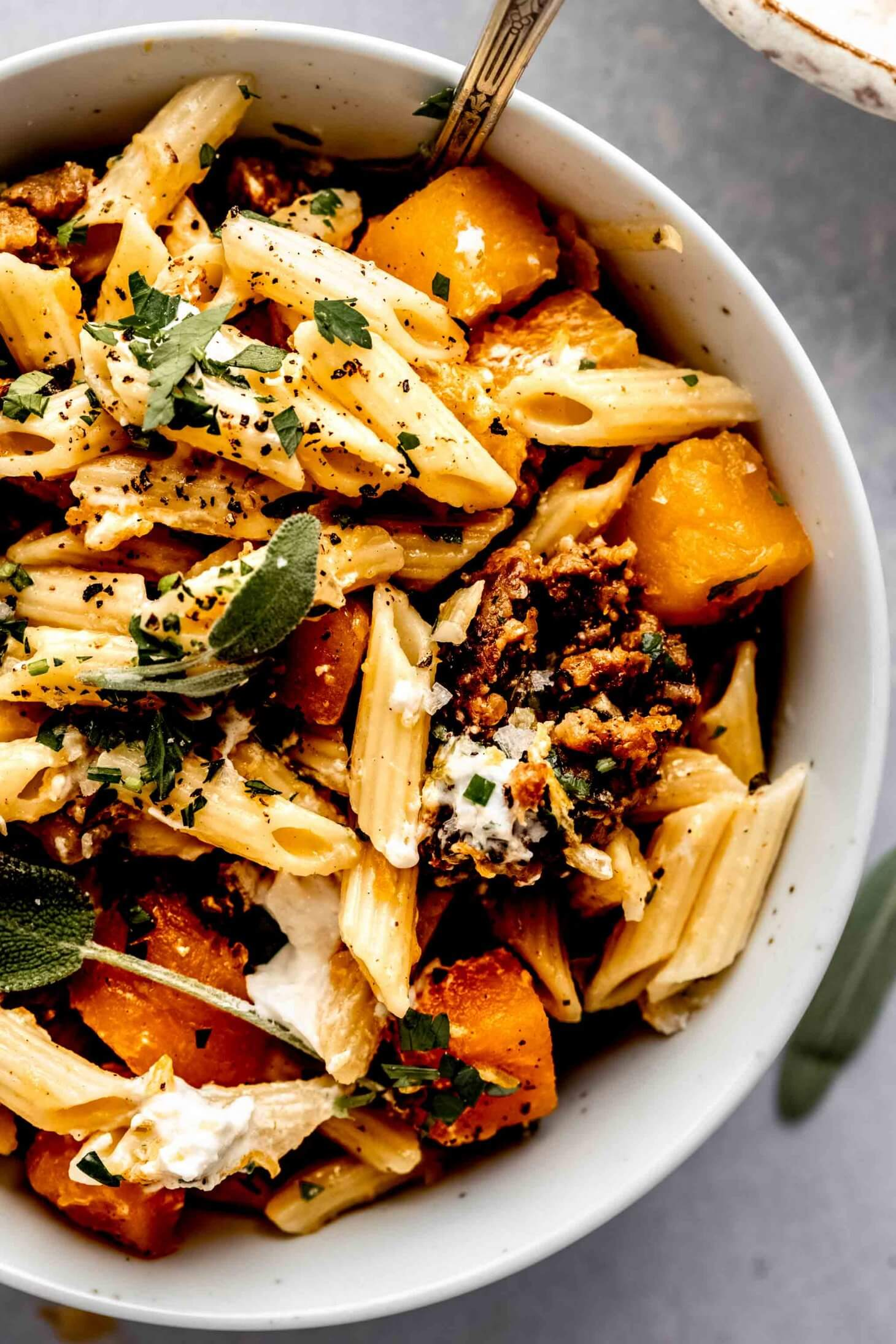 Butternut squash pasta in white bowl.