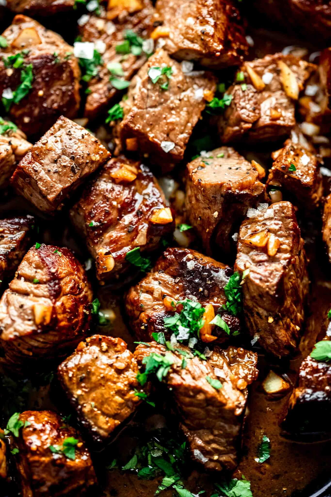 Overhead closeup of steak bites in skillet topped with garlic bits and parsley.