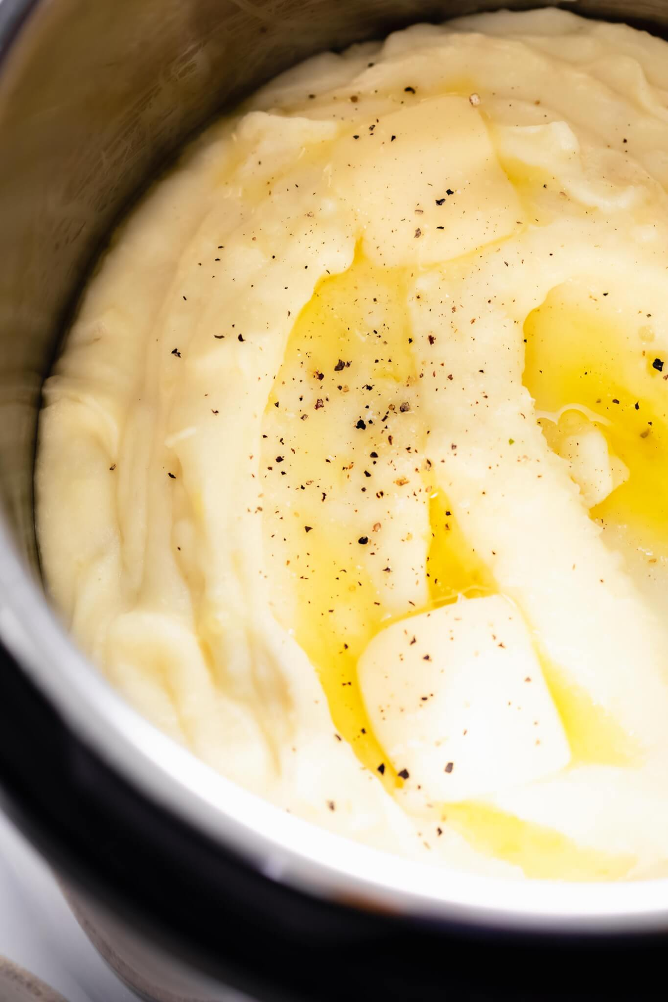 Mashed potatoes in instant pot topped with butter.