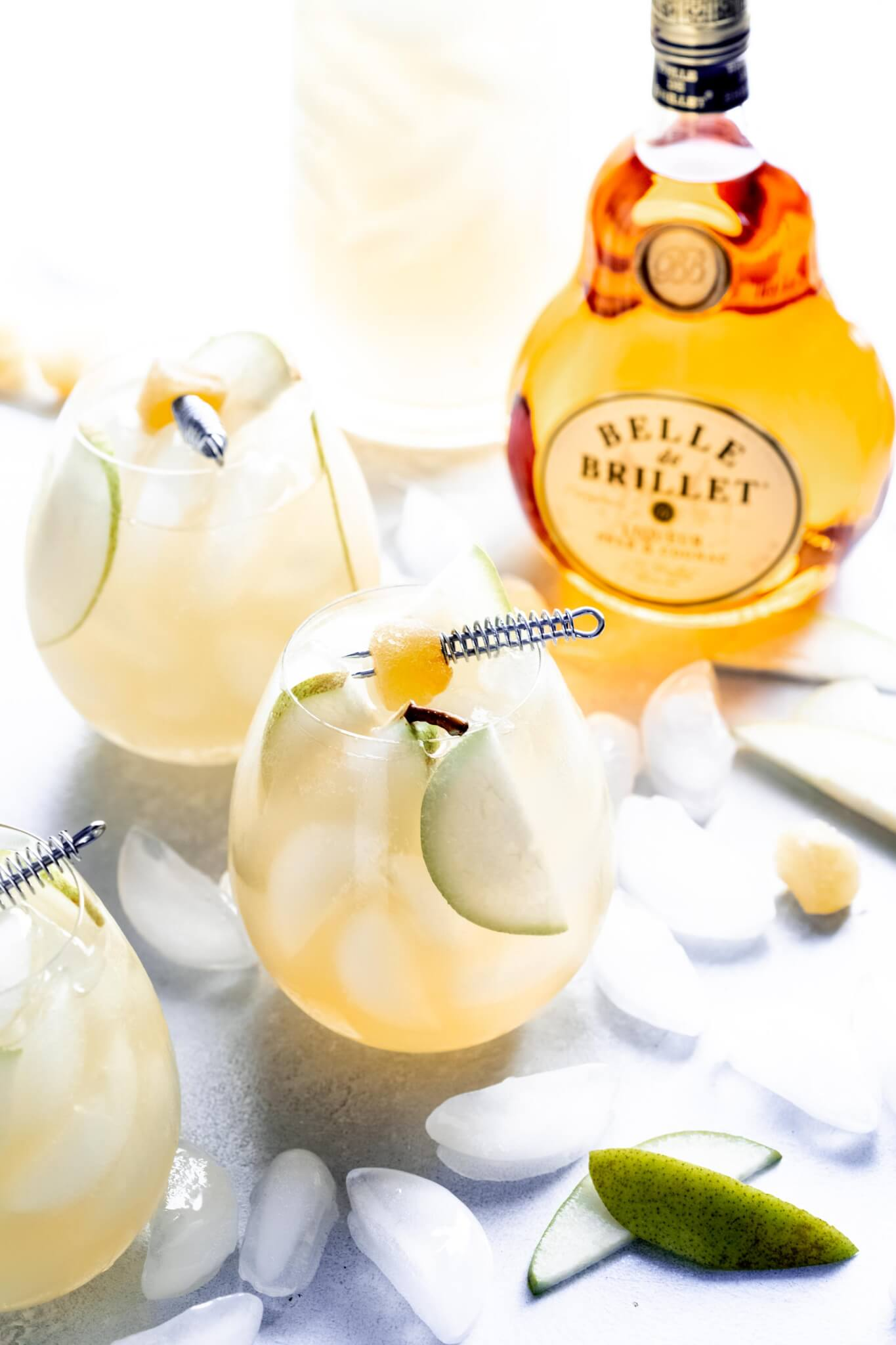 Three pear ginger sparkling cocktails spread on countertop with ice cubes and bowl of crystalized ginger and bottle of pear cognac.