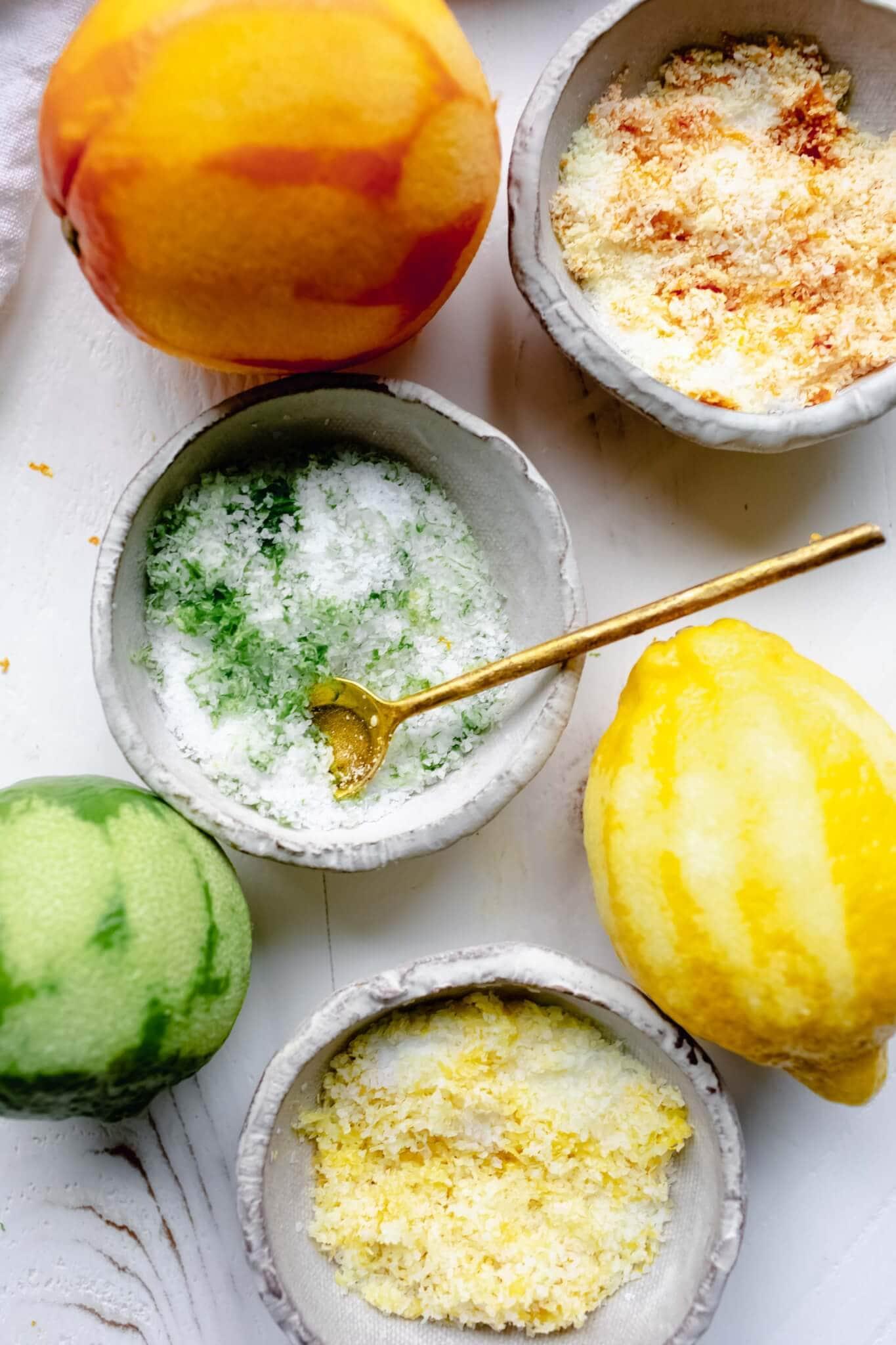 Overhead shot of three types of citrus salt - orange, lime and lemon