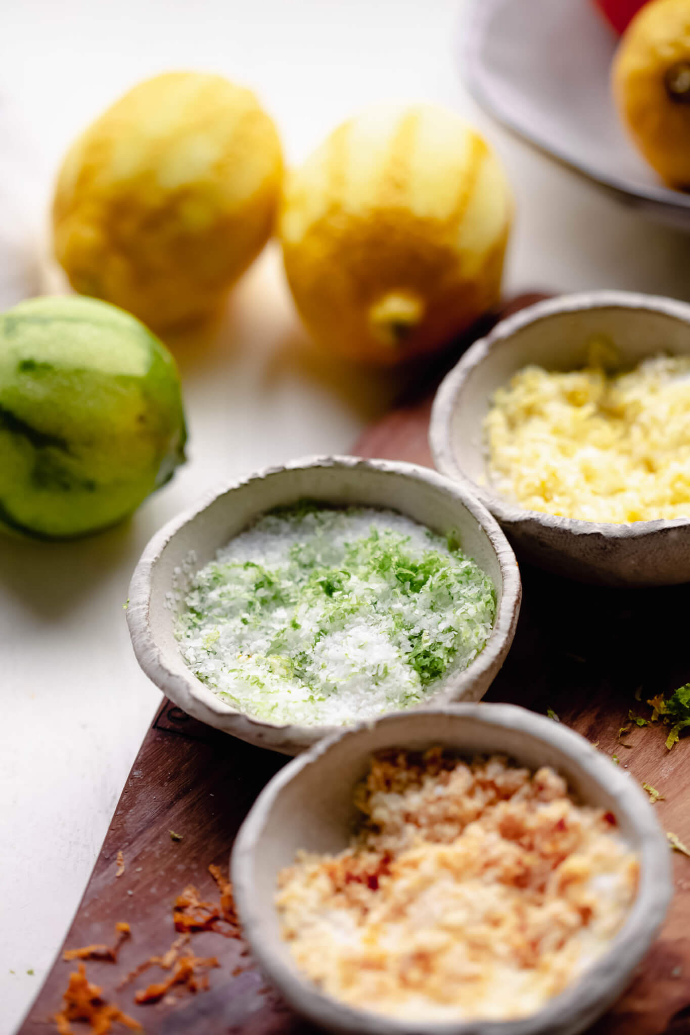 Three small bowls of lime, lemon and orange salt on cutting board next to zested citrus fruits.