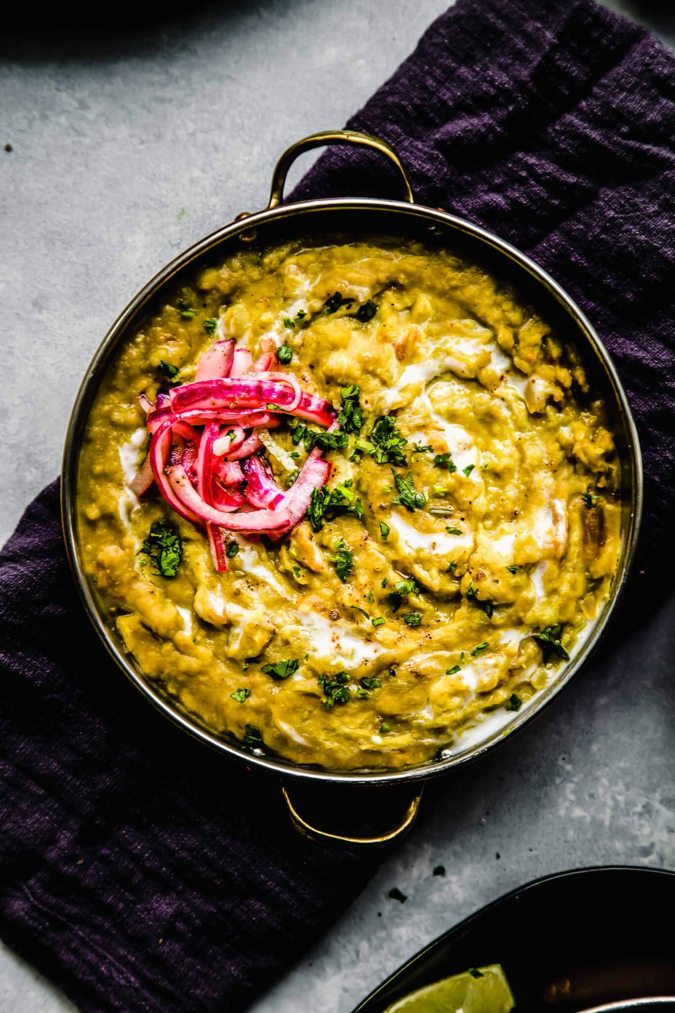 Overhead shot of dal topped with pickled onions in shallow bowl with handles.