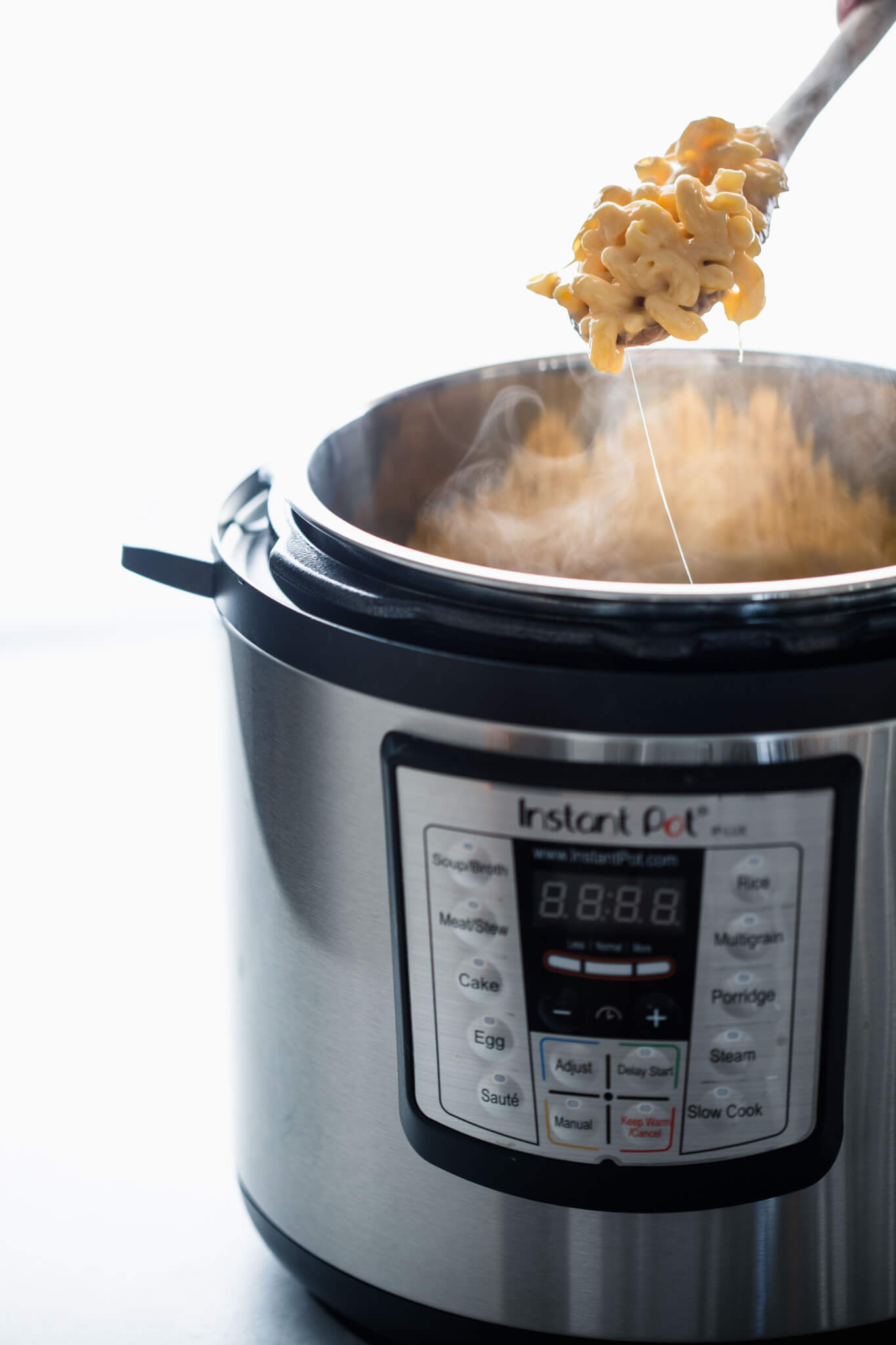 Side view of spoon pulling mac and cheese out of instant pot.
