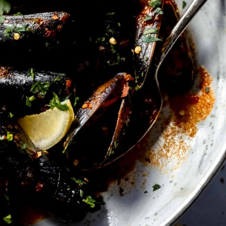 Mussels in large grey bowl after cooking served with lemon wedges.