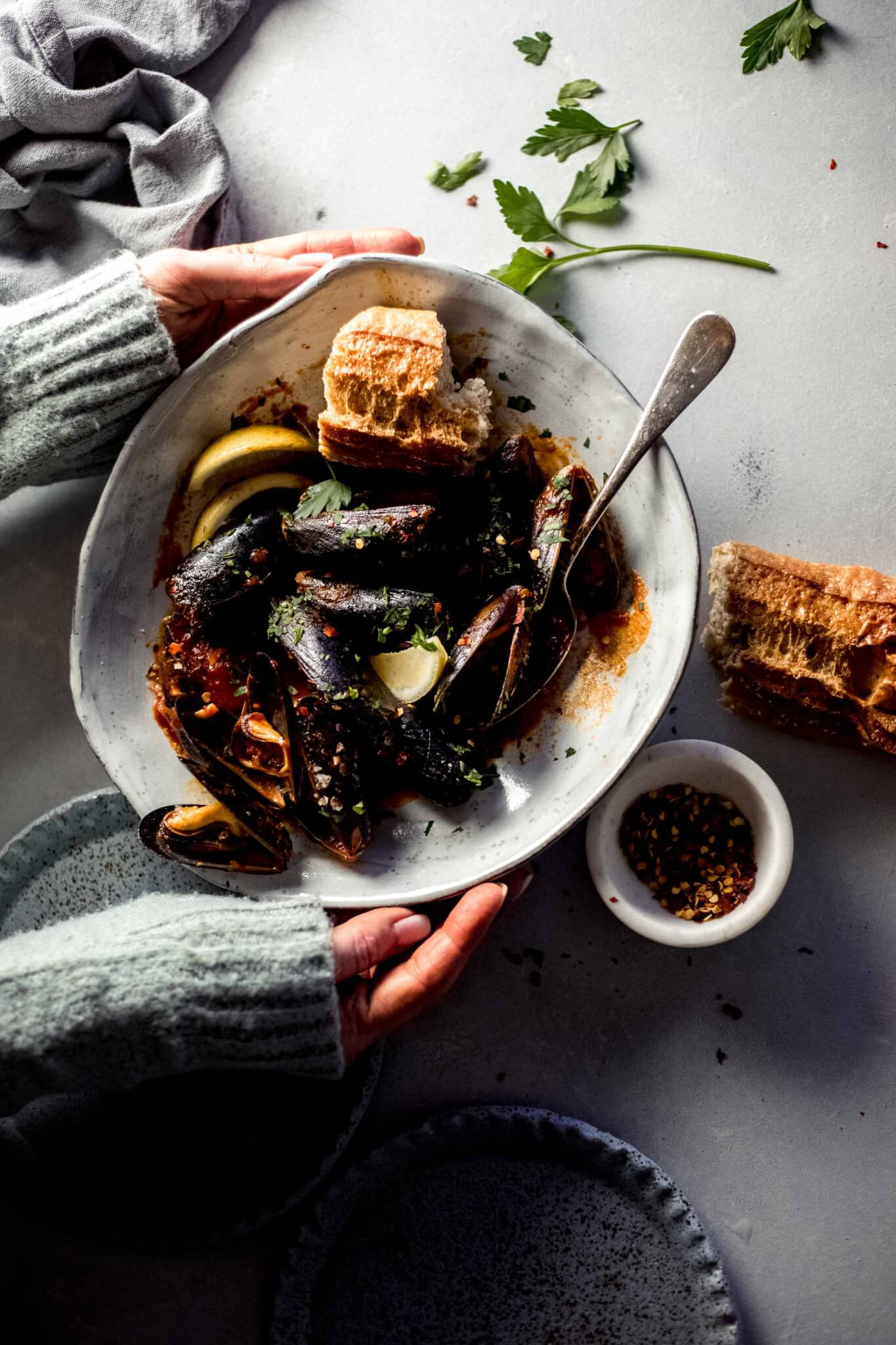 Two hands holding bowl of cooked mussels next to loaf of crusty bread and bowl of red pepper flakes.
