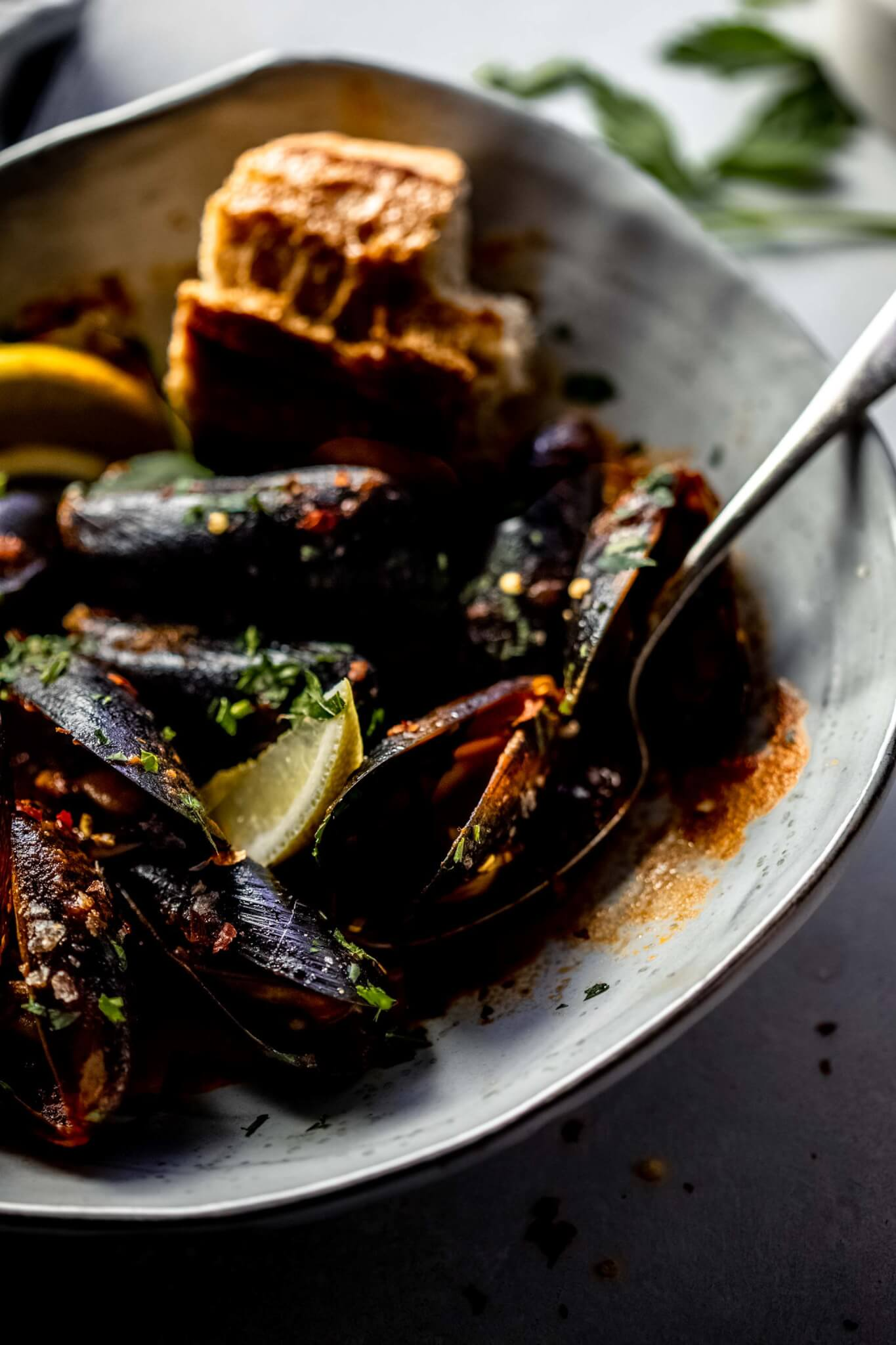 Side view of bowl of cooked mussels in marinara served with piece of baguette.