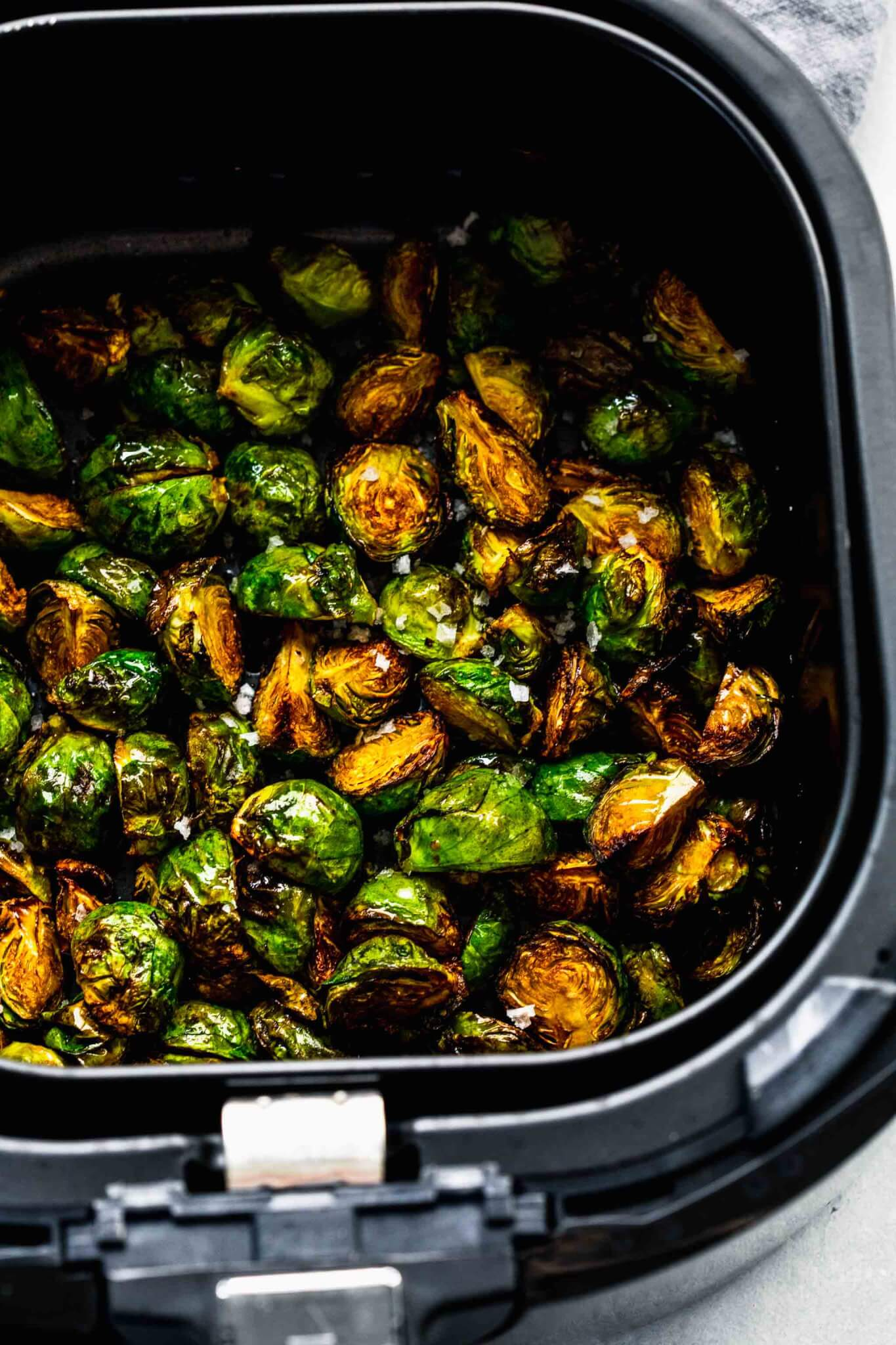 Cooked brussels sprouts in air fryer basket.