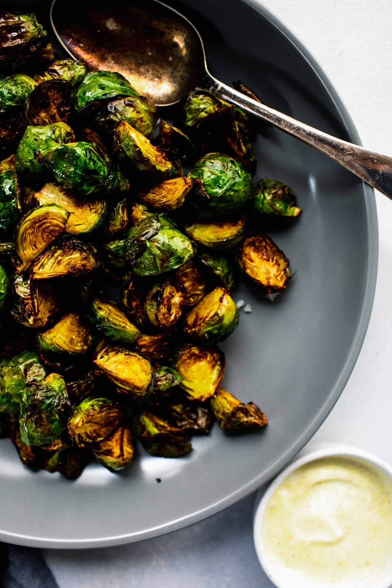 Over head shot of cooked brussels sprouts in grey bowl with spoon.