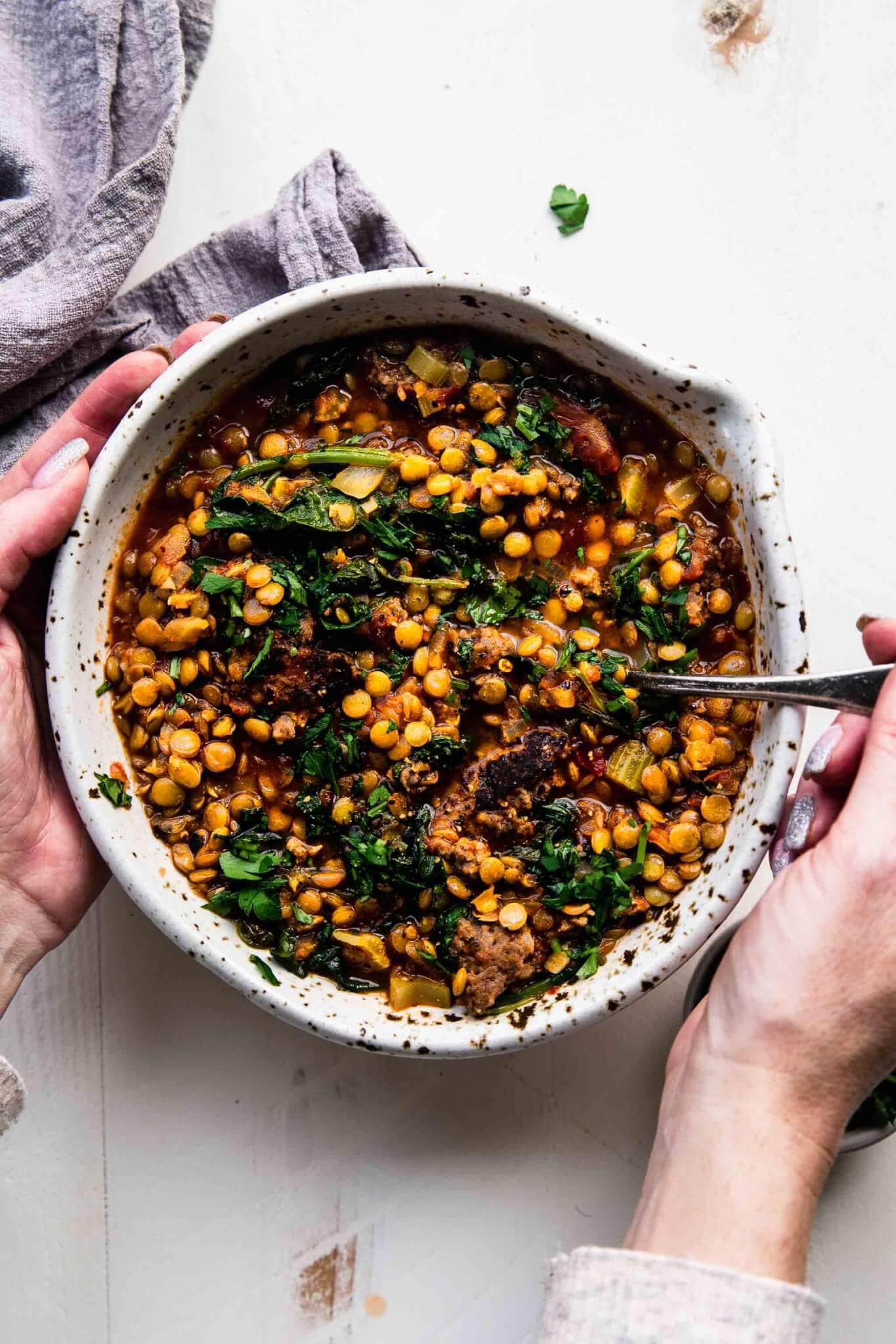 Two hands holding bowl of sausage kale lentil soup