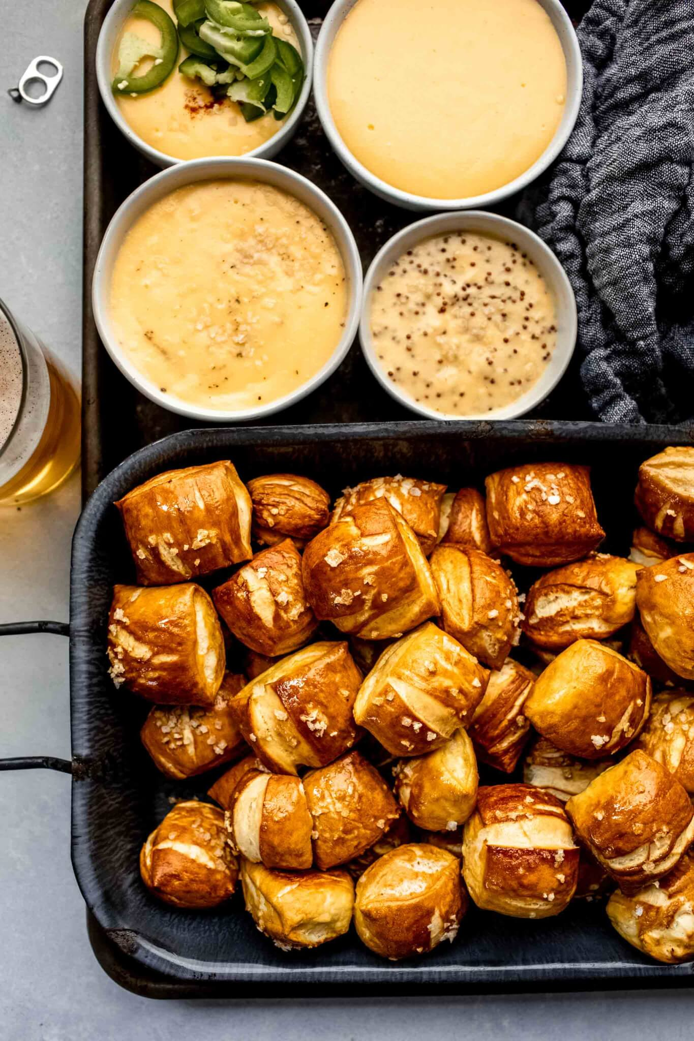 Overhead shot of pretzel bites on serving tray next to four types of cheese sauce.